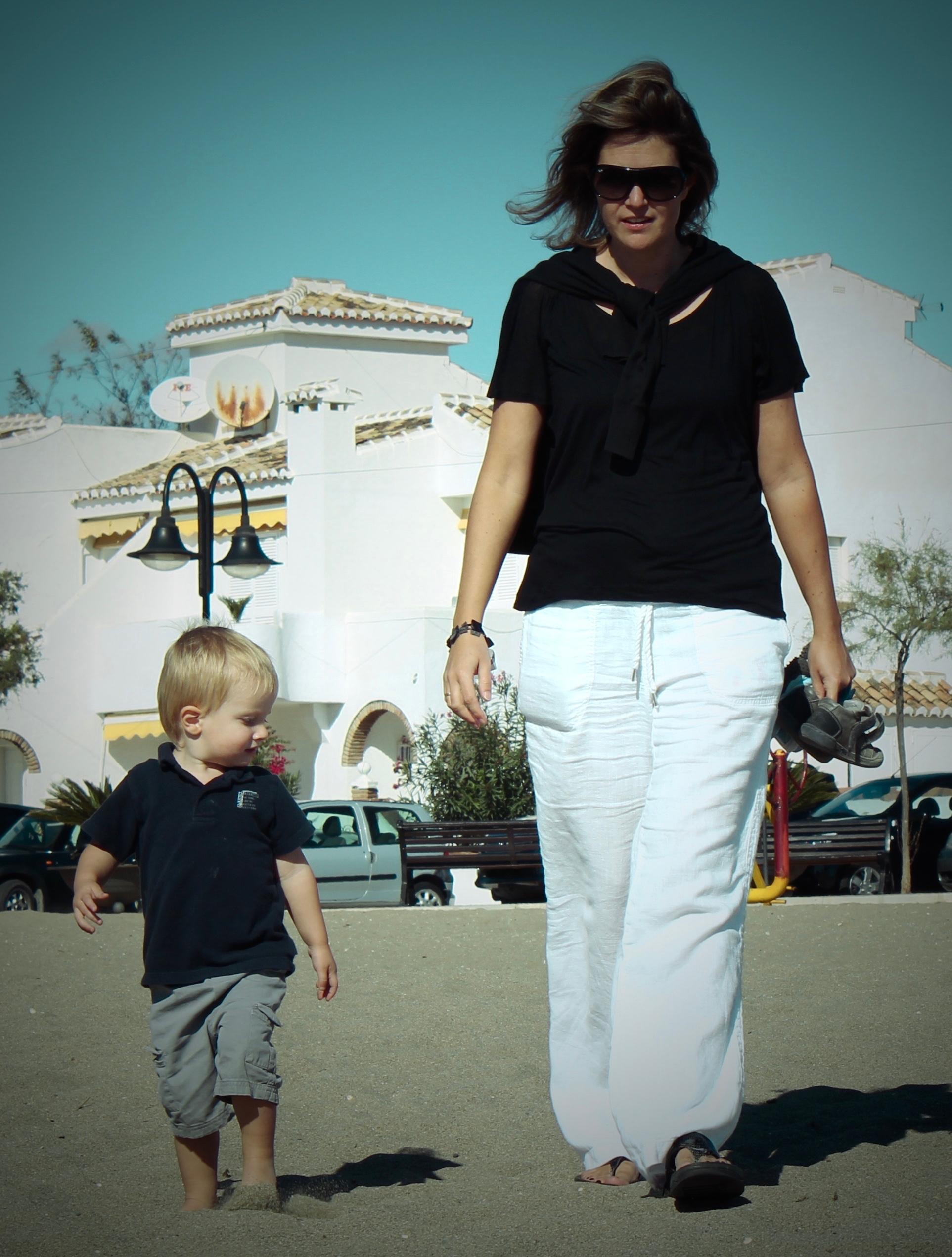 zoontje kijkt en imiteert hoe mama in het zand stapt