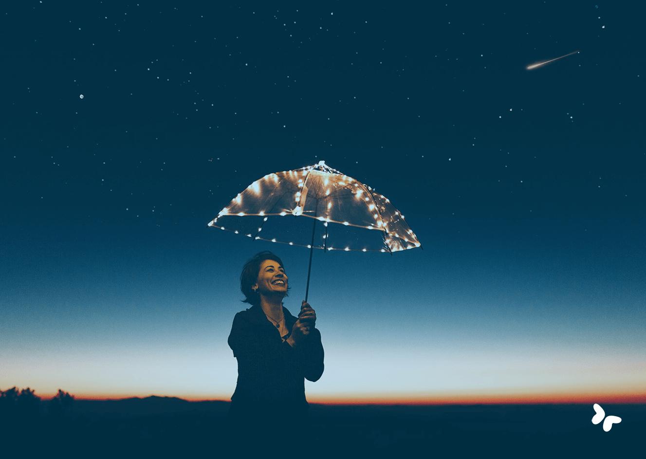 lachende vrouw met lichtgevende paraplu onder sterrenhemel