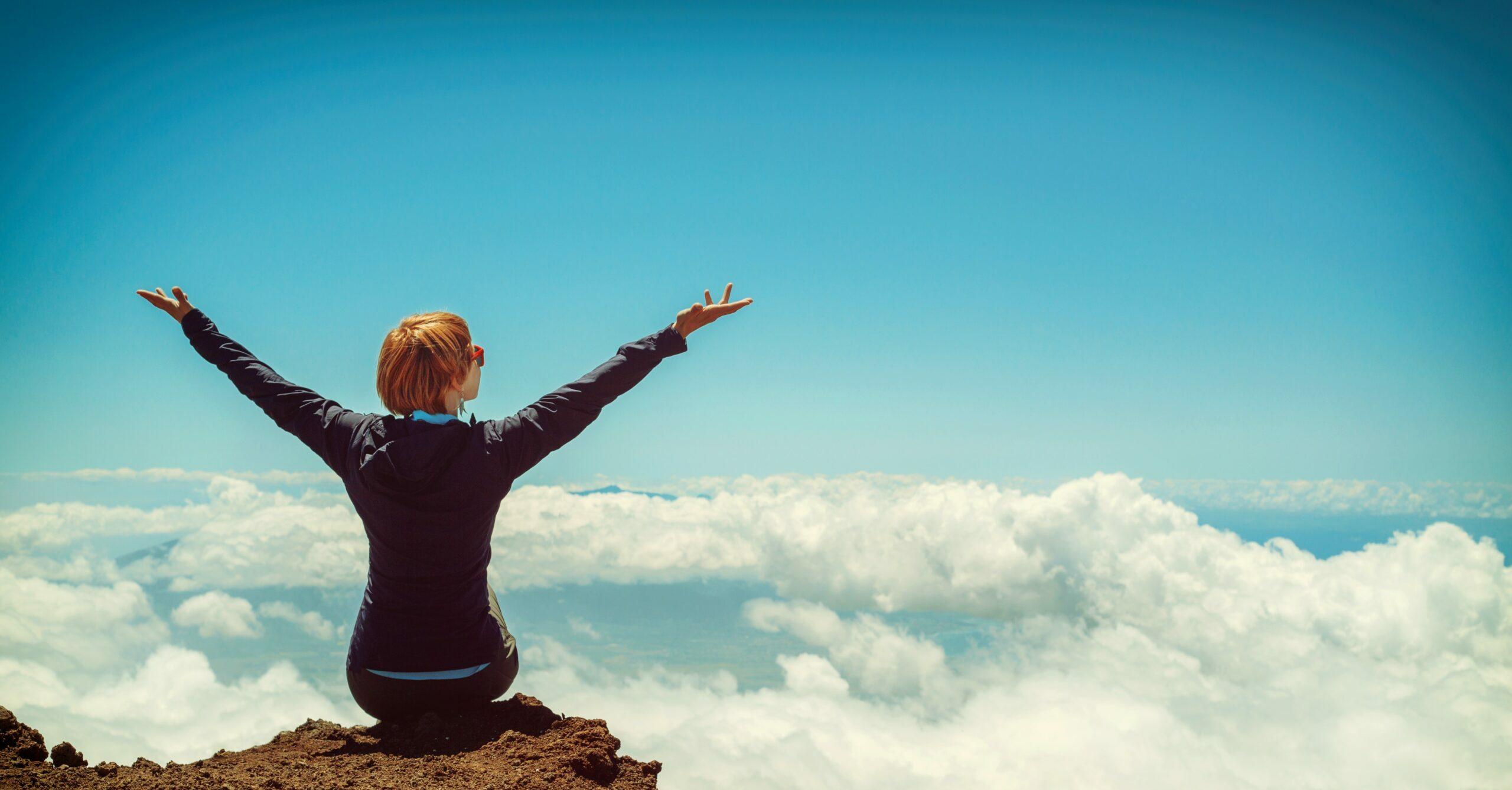 vrouw op rots boven de wolken vol geluk