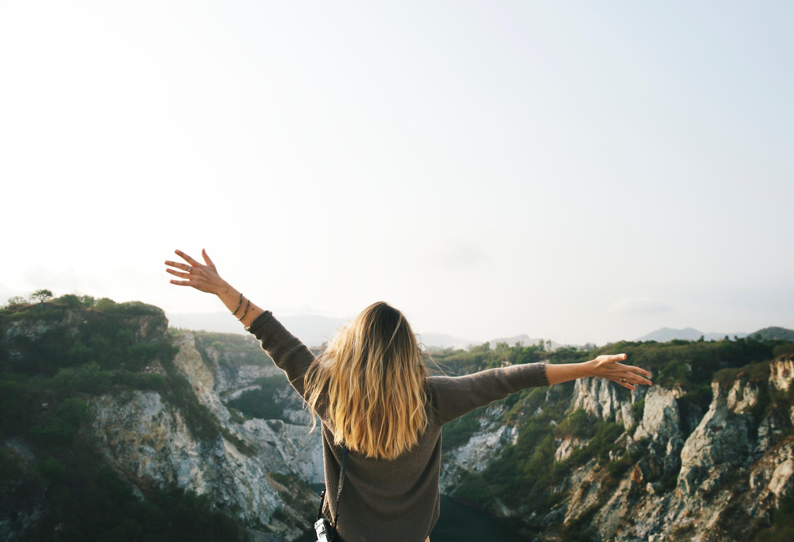 vrouw met open armen kijkt naar de vallei